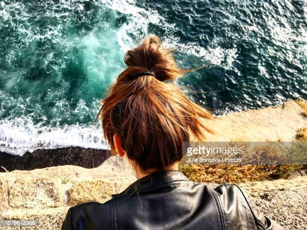 rear view of woman looking at sea - one young woman only stock pictures, royalty-free photos & images