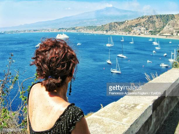 rear view of woman looking at sea - sizilien stock-fotos und bilder