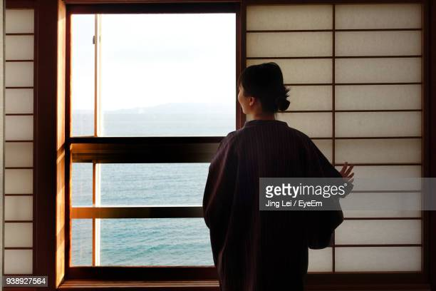 rear view of woman looking at sea through window - 指宿市 ストックフォトと画像