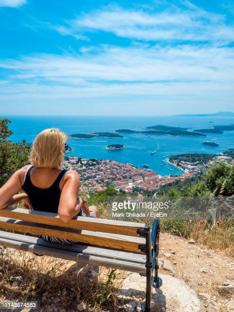 rear view of woman looking at sea while sitting on bench against blue sky - hvar stock photos and pictures