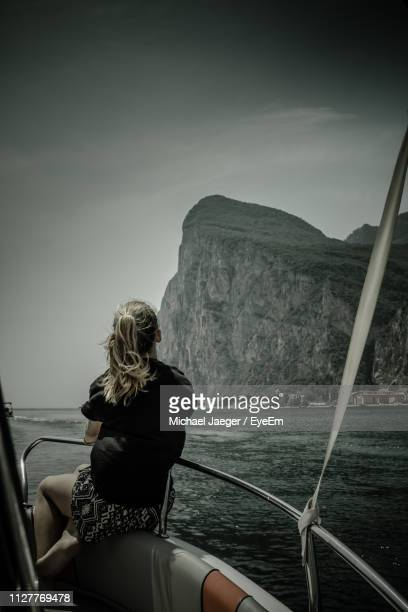 rear view of woman looking at sea while sitting on boat against mountain - michael jaeger stock pictures, royalty-free photos & images
