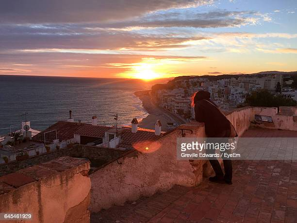 Rear View Of Woman Looking At Sea While Standing On Building Terrace During Sunset