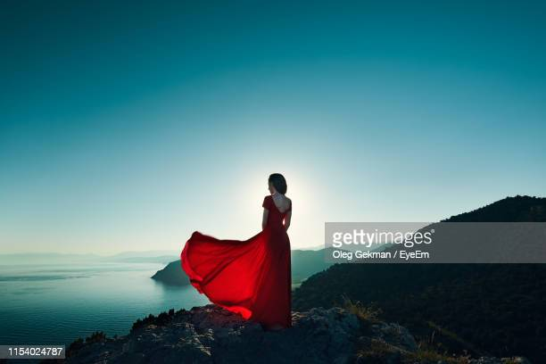 rear view of woman looking at sea while standing on cliff against clear sky during sunset - blue dress stock pictures, royalty-free photos & images