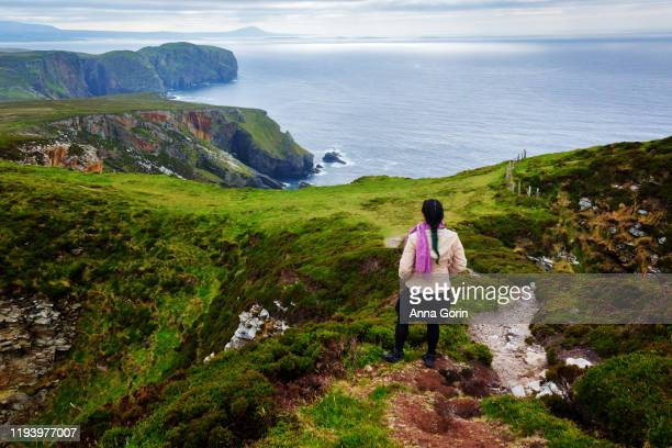 rear view of woman looking at steep cliffs of horn head and north atlantic ocean on overcast day in county donegal, ireland - contea di donegal foto e immagini stock
