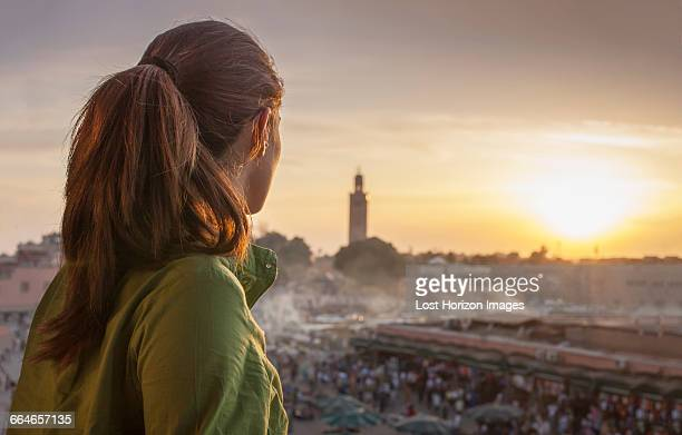 Rear view of woman looking at sunset over Jemaa el-Fnaa Square, Marrakesh, Morocco