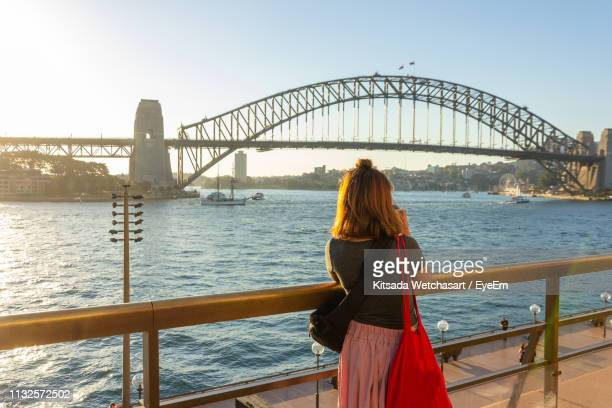 rear view of woman looking at sydney harbor bridge over river against sky - tourism stock pictures, royalty-free photos & images