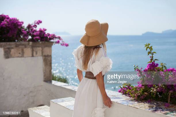 rear view of woman looking at the sea, wearing a beautiful white dress - white dress stock pictures, royalty-free photos & images