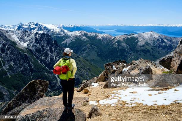 rear view of woman looking at view while standing on mountain during winter - bariloche fotografías e imágenes de stock
