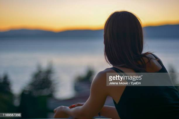 rear view of woman looking away while sitting outdoors during sunset - jelena ivkovic stock pictures, royalty-free photos & images
