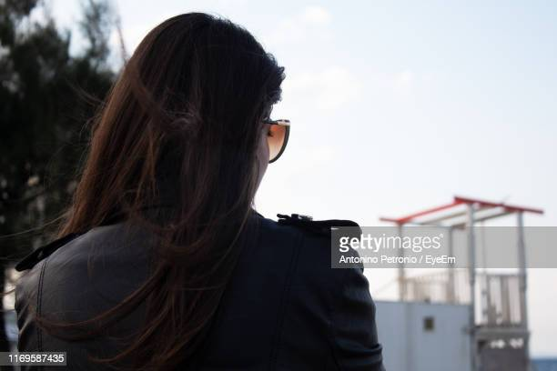 rear view of woman looking away while standing against sky - one young woman only stock pictures, royalty-free photos & images