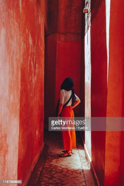 rear view of woman looking away while standing in corridor of building - femme marocaine photos et images de collection