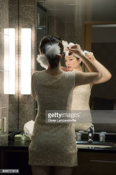rear view of woman looking in bathroom mirror - japanese short skirts stock photos and pictures