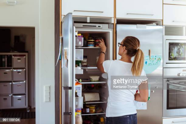 rear view of woman looking into refrigerator while standing in kitchen - geladeira - fotografias e filmes do acervo