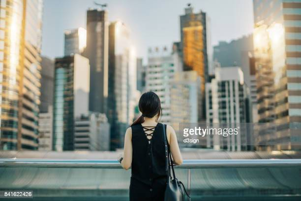 rear view of woman looking out over urban cityscape against sky - back to work stock pictures, royalty-free photos & images