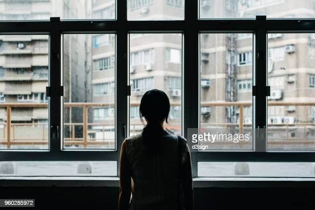 rear view of woman looking out to city through window - negative emotion stock pictures, royalty-free photos & images