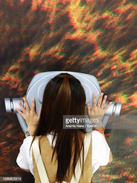 Rear View Of Woman Looking Through Coin-Operated Binoculars At Sky