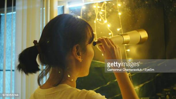 Rear View Of Woman Looking Through Telescope At Home