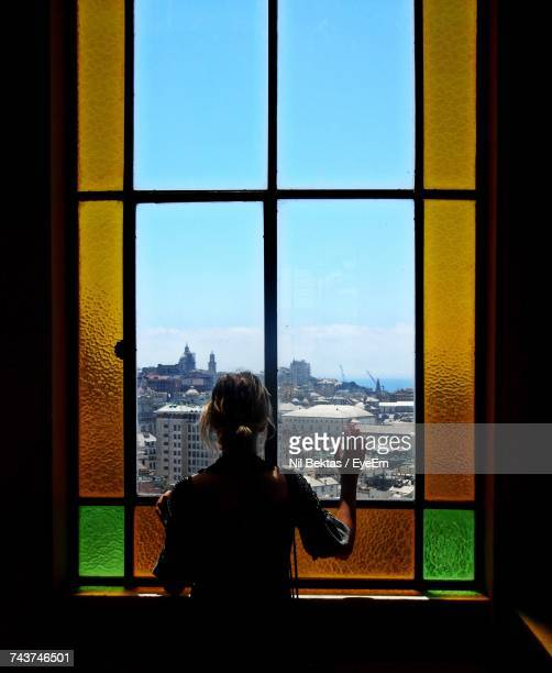 rear view of woman looking through window - one young woman only stock pictures, royalty-free photos & images