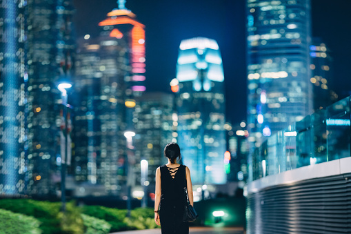 Rear view of woman looking towards contemporary financial skyscrapers in downtown area of Hong Kong - gettyimageskorea