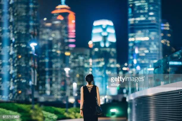 rear view of woman looking towards contemporary financial skyscrapers in downtown area of hong kong - projection stock pictures, royalty-free photos & images