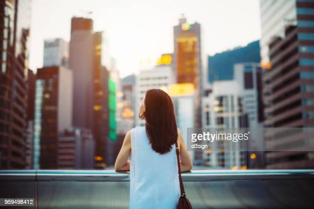 rear view of woman looking up to sky with smile on a fresh bright morning in city - verandering stockfoto's en -beelden