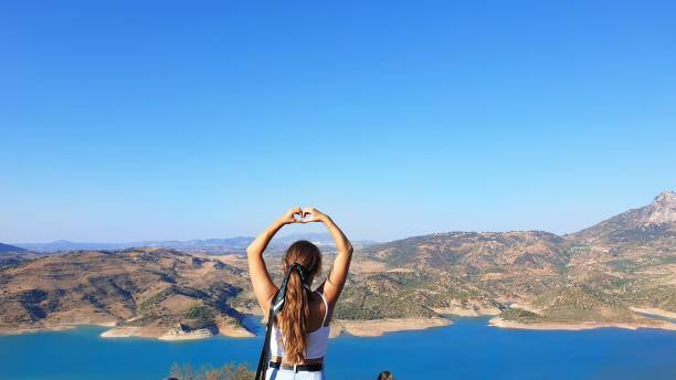 Rear View Of Woman Making Heart Shape Against Mountain And Sky