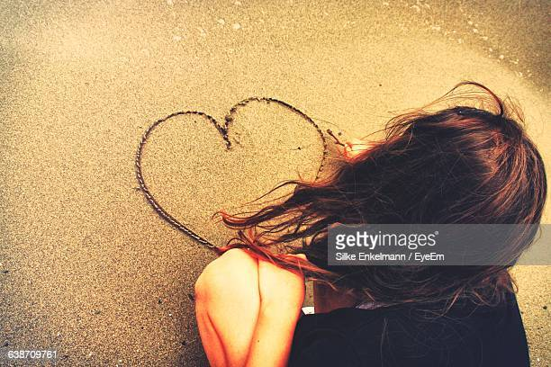 Rear View Of Woman Making Heart Shape On Sand At Beach