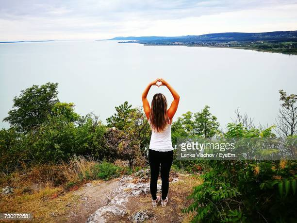 Rear View Of Woman Making Heart Shape While Standing On Cliff Against Sea