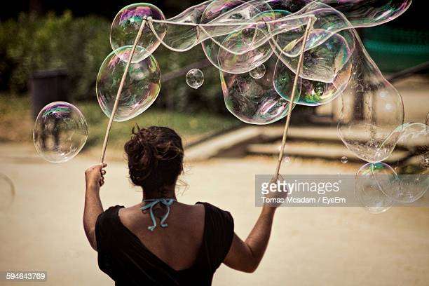 Rear View Of Woman Making Large Bubbles On Street