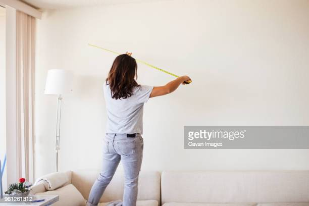 rear view of woman measuring wall while standing on sofa at home - cheveux mi longs photos et images de collection