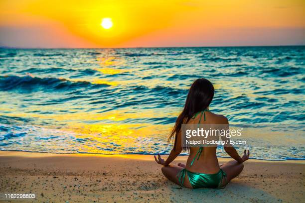 rear view of woman mediating at beach during sunset - chanthaburi sea stock pictures, royalty-free photos & images