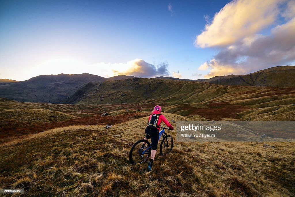 Rear View Of Woman Mountain Biking Against Sky : Stock Photo