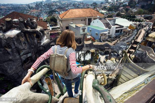 Rear view of woman moving down steps over cityscape