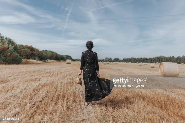 rear view of woman on agricultural field against sky - elegancia fotografías e imágenes de stock
