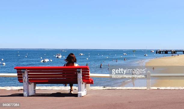 rear view of woman on beach against clear blue sky - aquitaine stock photos and pictures