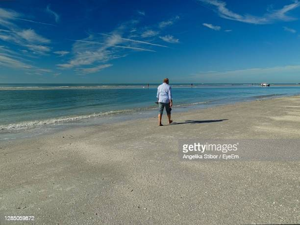 rear view of woman on beach against sky - siesta key stock pictures, royalty-free photos & images