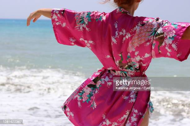 rear view of woman on beach - robe à motif floral photos et images de collection