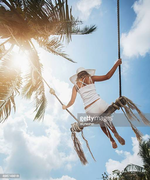 Rear view of woman on beach swing against sky.