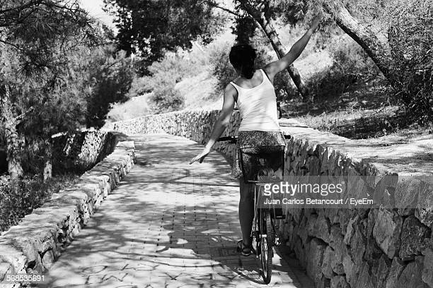 rear view of woman on bicycle with arms raised - hands free cycling stock pictures, royalty-free photos & images