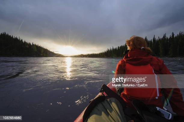 rear view of woman on boat in river against cloudy sky - marek stefunko imagens e fotografias de stock
