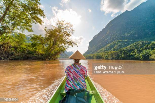 rear view of woman on boat in river against sky - mekong delta stock pictures, royalty-free photos & images