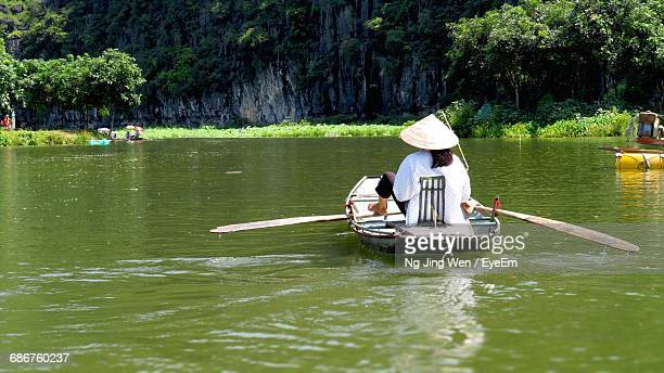 Rear View Of Woman On Boat With Asian Style Conical Hat In River During Sunny Day