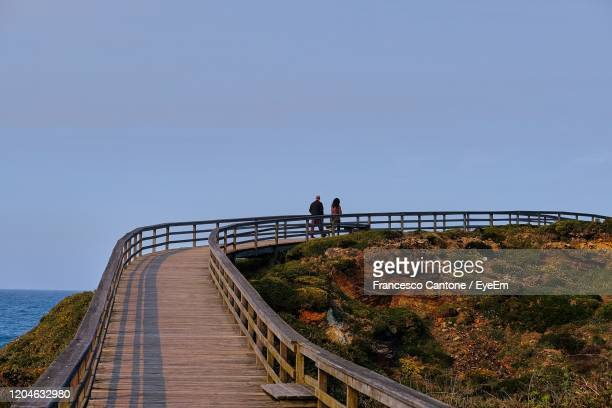 rear view of woman on bridge over sea - oviedo stock pictures, royalty-free photos & images