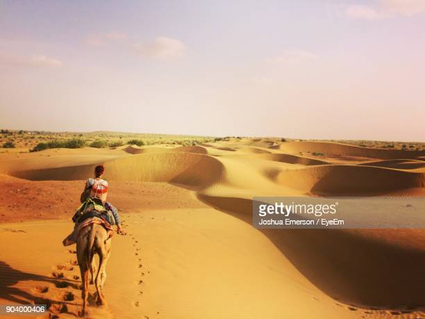 Rear View Of Woman On Camel In Desert Against Sky