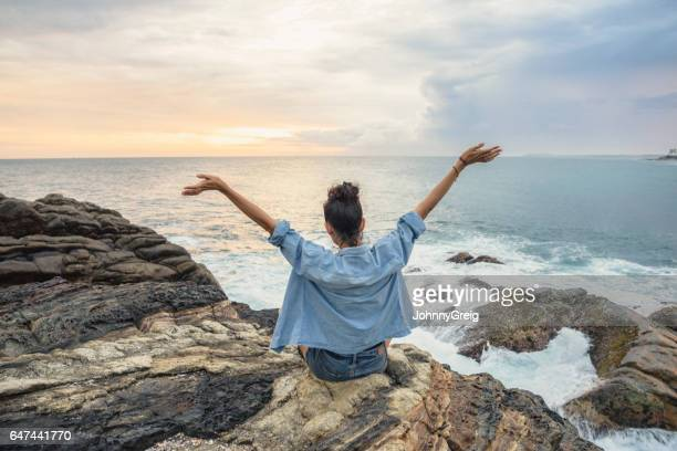 Rear view of woman on coastline with arms outstretched