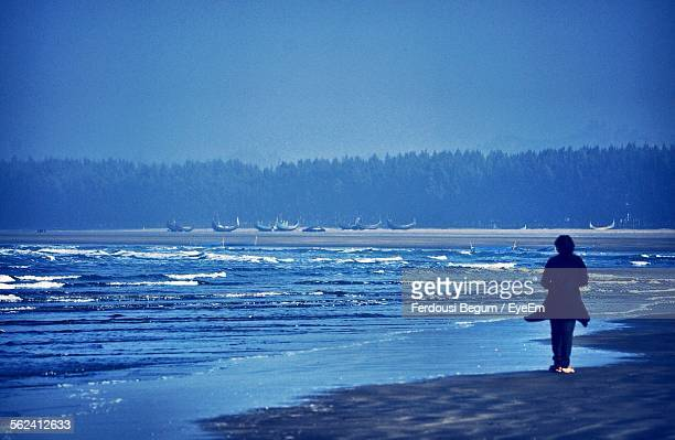 rear view of woman on coxs bazaar beach against sky - coxs bazaar stock photos and pictures