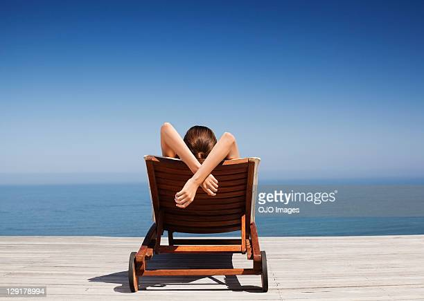 rear view of woman on deck chair - outdoor chair stock pictures, royalty-free photos & images