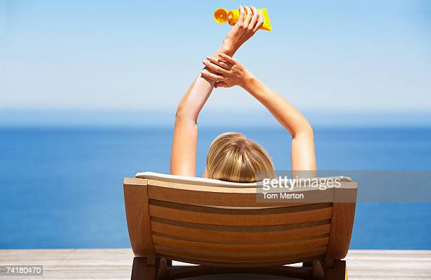 rear view of woman on folding chair outdoors applying sun block or suntan lotion - sunscreen stock photos and pictures