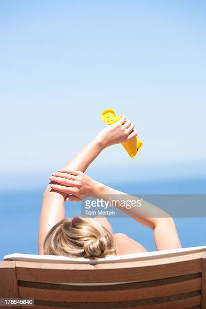 Rear view of woman on folding chair outdoors applying sunblock