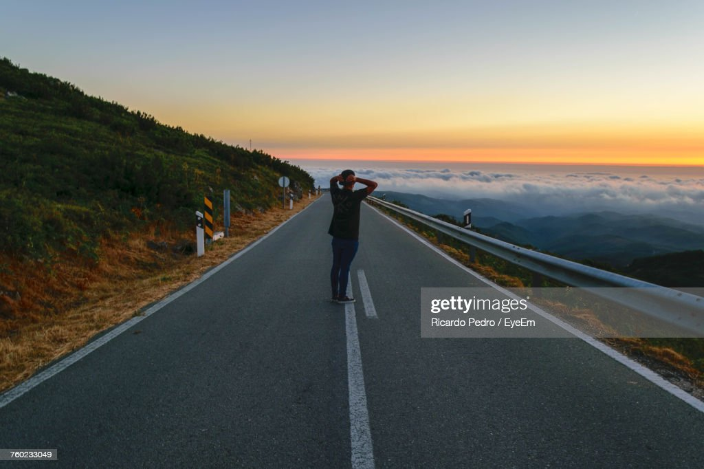 Rear View Of Woman On Road Against Sky During Sunset : ストックフォト
